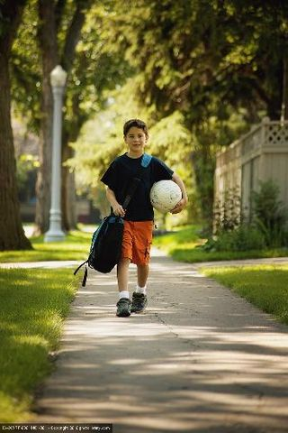 Boy walking with bag, soccer ball